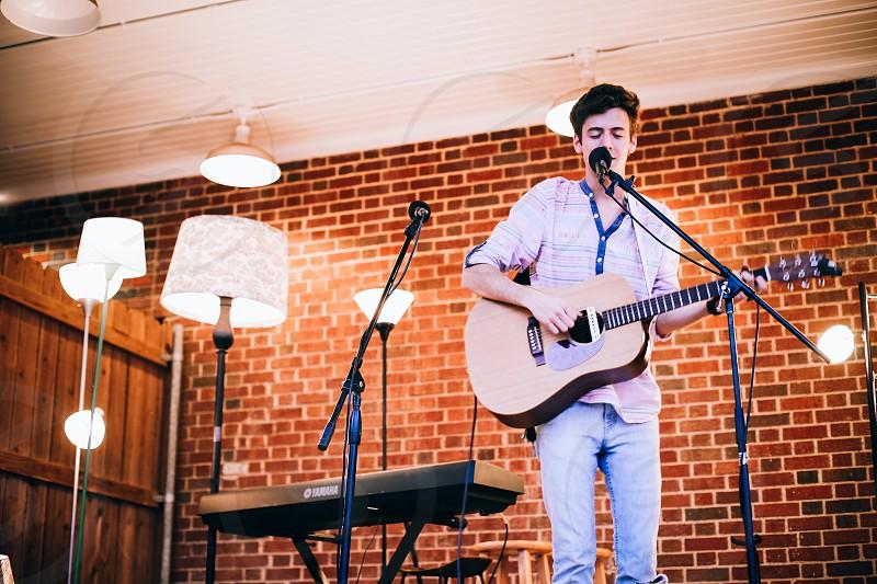 boy playing guitar while singing photo
