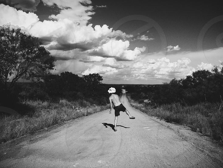 boy in black shorts walking on grey dirt road photo