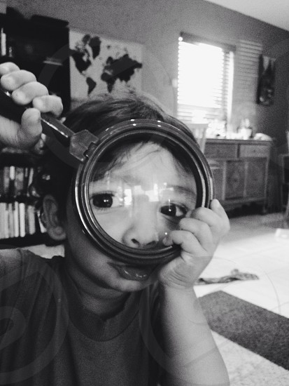 A little boy looks through a magnifying glass photo