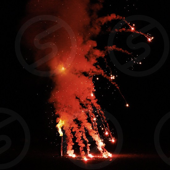 red firework and smoke bomb exploding in black night photo