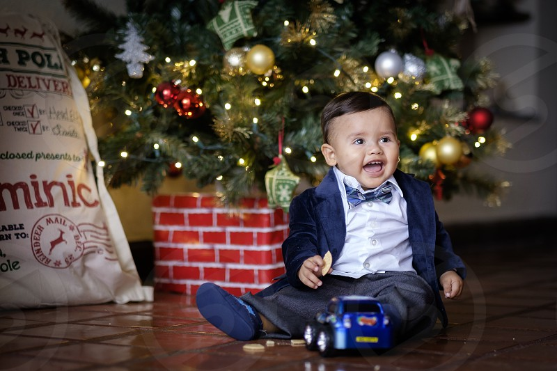 Cute hispanic baby child formally dressed enjoying Christmas day with new toy car. photo