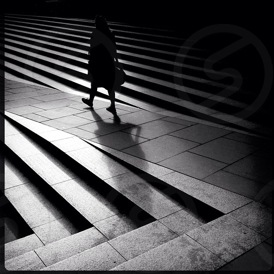 A woman walks between steps as the low afternoon sun casts long shadows. photo