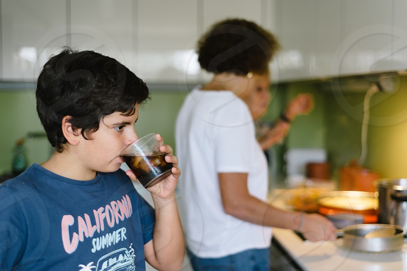 Multigeneration family preparing food in domestic kitchen photo