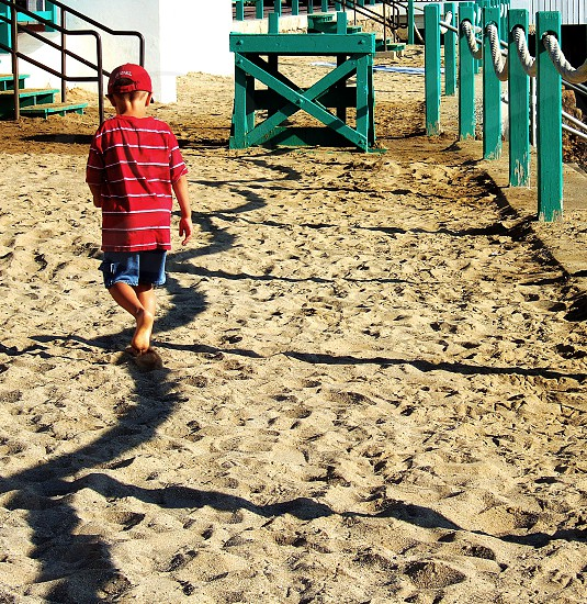 Little boy walks a curved shadow line on sand. The shadow is made by a rope fence. photo