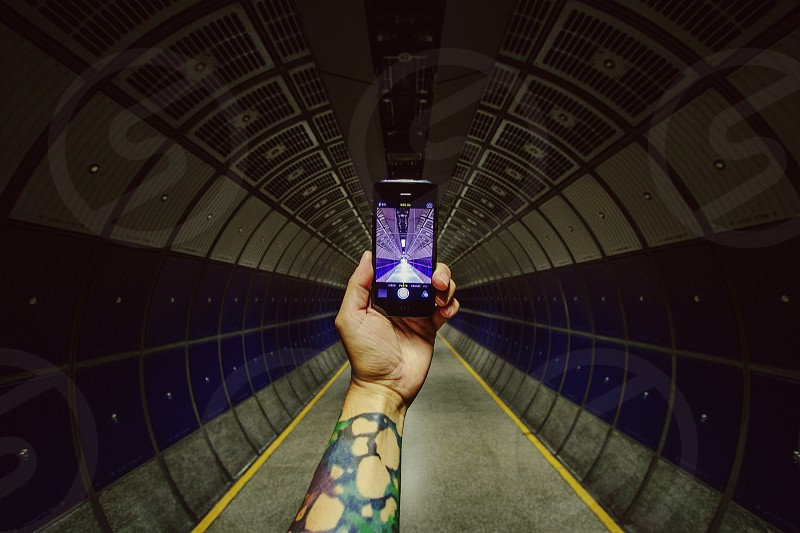 man with tattooed arms aiming smartphone on tunnel photo