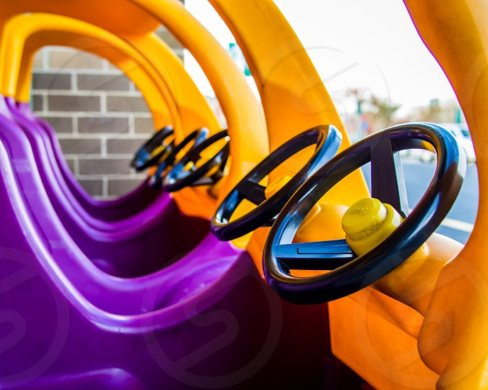 A line up of children's purple and yellow pretend driving carts / cars.  These are the front portions of a set of shopping carts with an area for for kids to pretend they are at the wheel driving the cart.  The shapes of the cars make an interesting pattern. photo