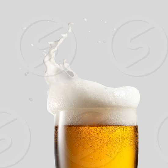 Close-up of cold beer with foam and splash on a gray background photo