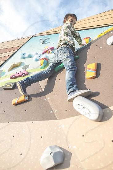 Child climb a climbing wall. Playground photo