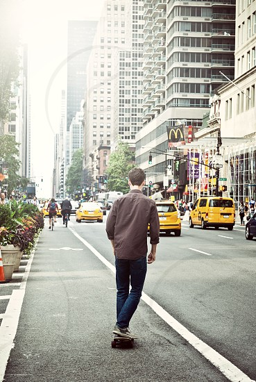 Young man with skateboard from behind in the center of Manhattan in New York City USA photo