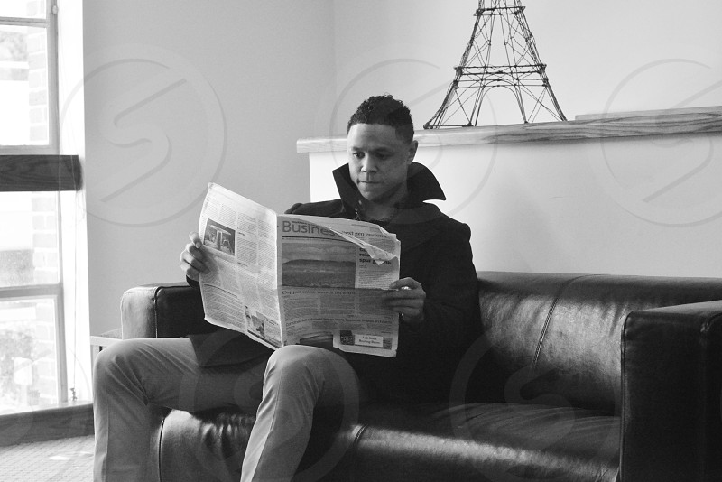 man in black jacket reading newspaper while sitting on black leather couch photo