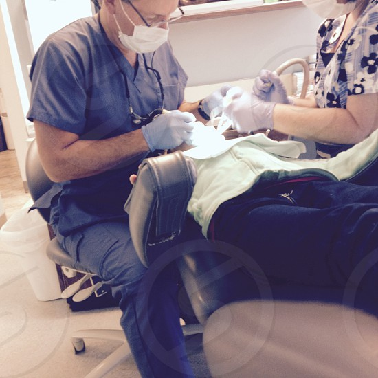 Little girl getting fillings at the dentist with the help of the dentist assistant. photo