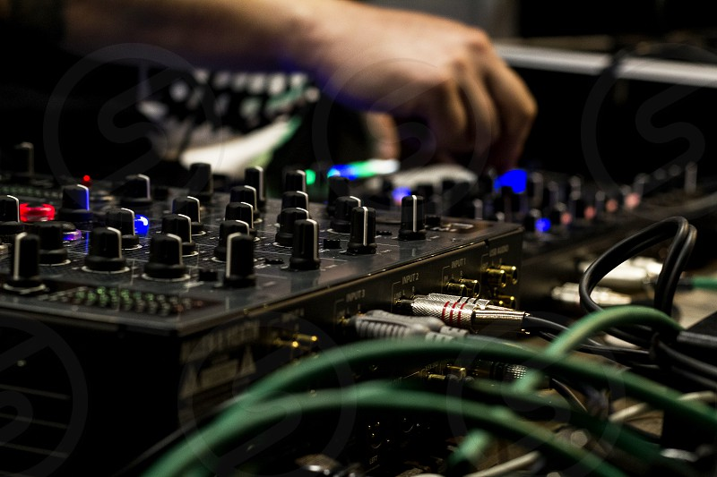 The dj uses the mixer to create electronic music live. photo