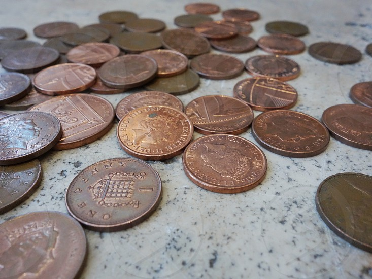 A selection of copper one penny coins loosely laid on a marble surface... photo