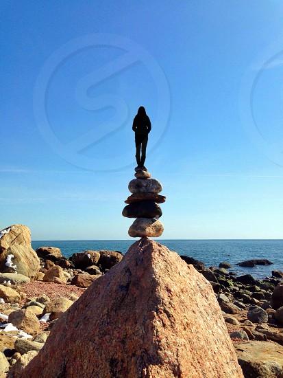 woman silhouette above rocks photo