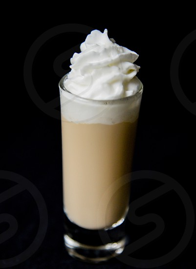 beige latte on top with whip cream in a clear drinking glass photo
