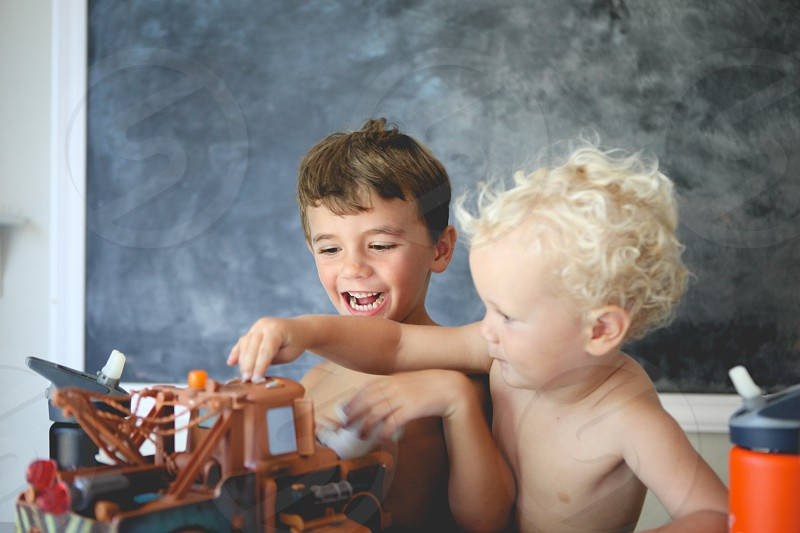 two toddlers with up dress playing with brown wooden toy photo