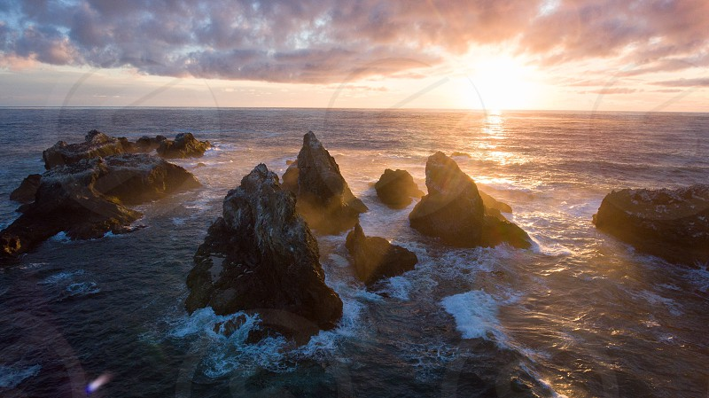 sea waves hitting rock formation under white clouds and sun photo