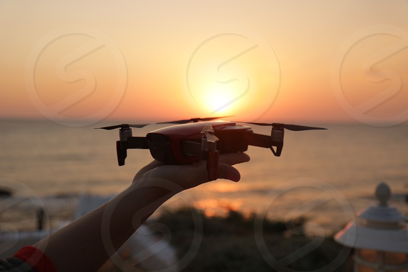 Drone action holding hand sunrise summer travel vacation sea water closeup photo