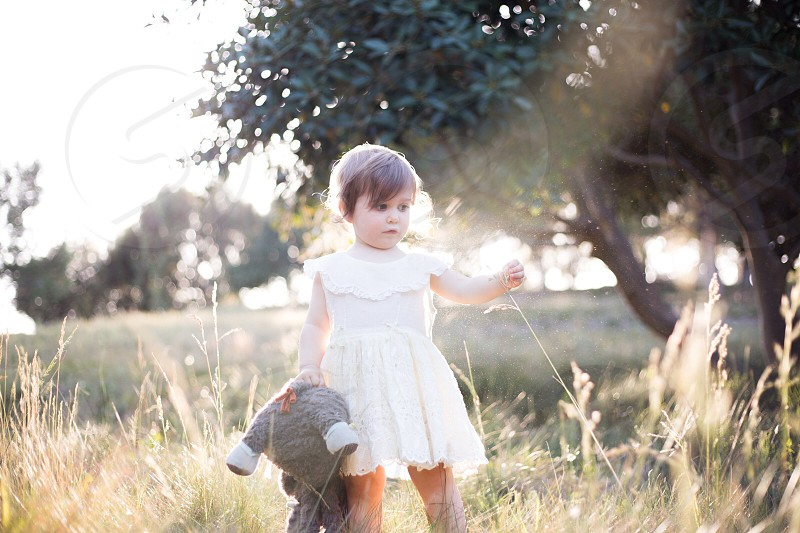 girl in white sleeveless dress carrying gray and white plush toy surrounded by green grass near trees photo