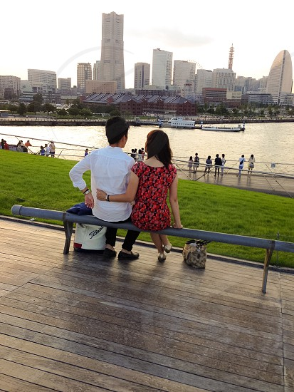 man and woman sitting on gray metal bench photo
