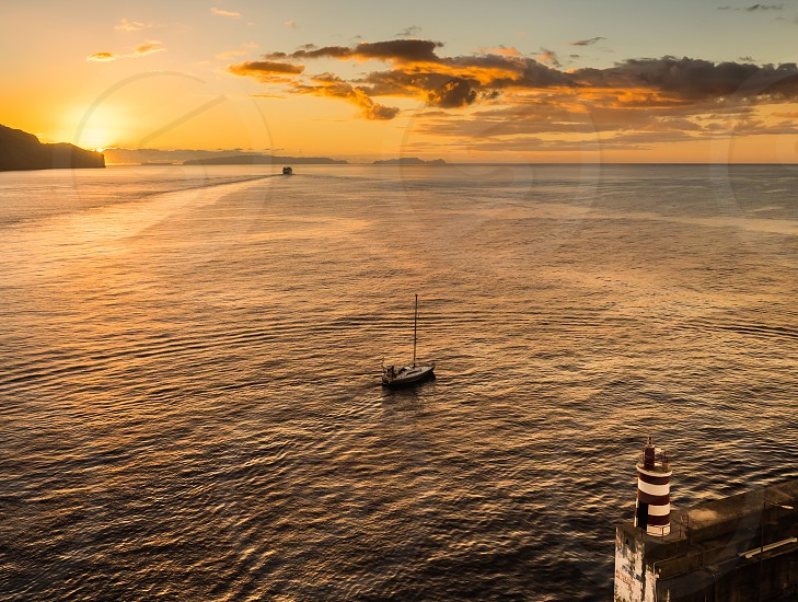 A ferry and a sailing boat leave the port on a golden morning under the safety of the port wall and light. photo