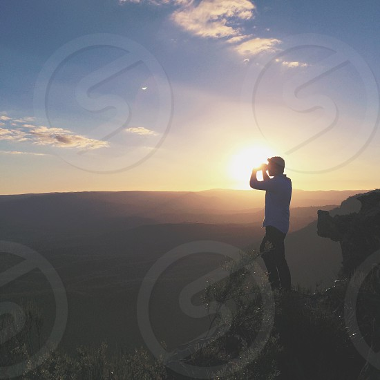man in blue shirt and black pants standing near ledge while watching sunrise photo