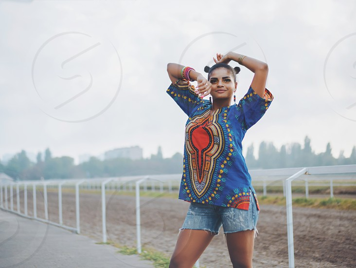 Happy beautiful afro-american woman outdoor. Young mixed race carefree girl wearing colorful clothing enjoys the day. Black Lady posing at summer as model photo