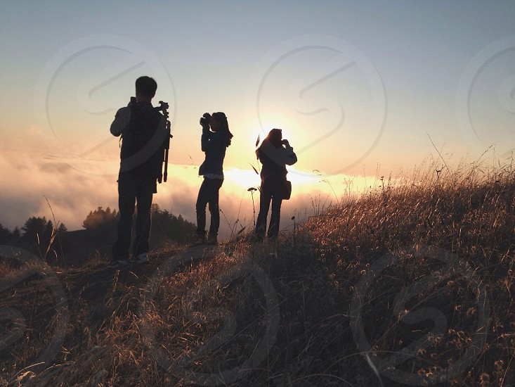 three standing figures holding cameras  on brown grass hill photo