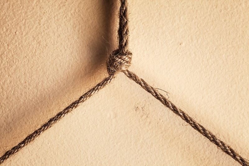 Abstract composition of small ropes and knot over the wall.  photo