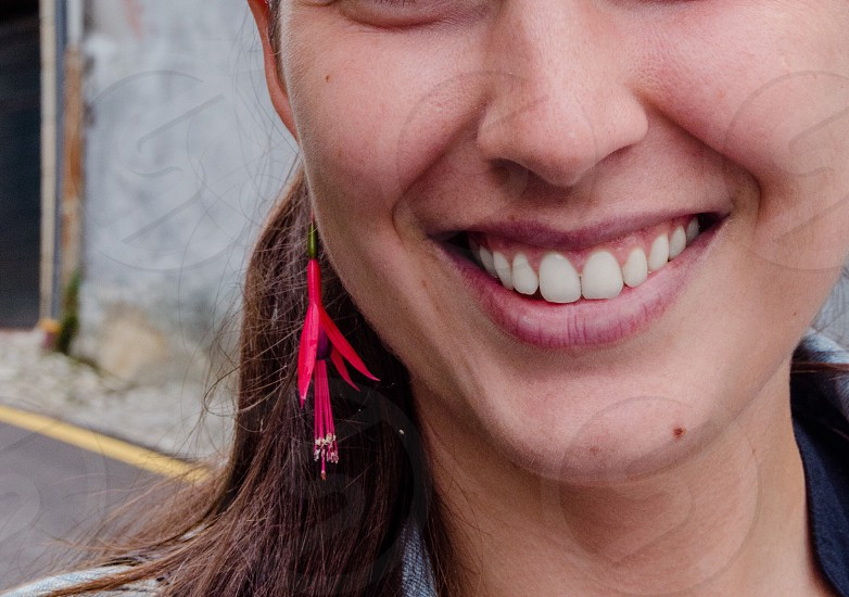 close up photo of woman with red dangling earrings smiling photo