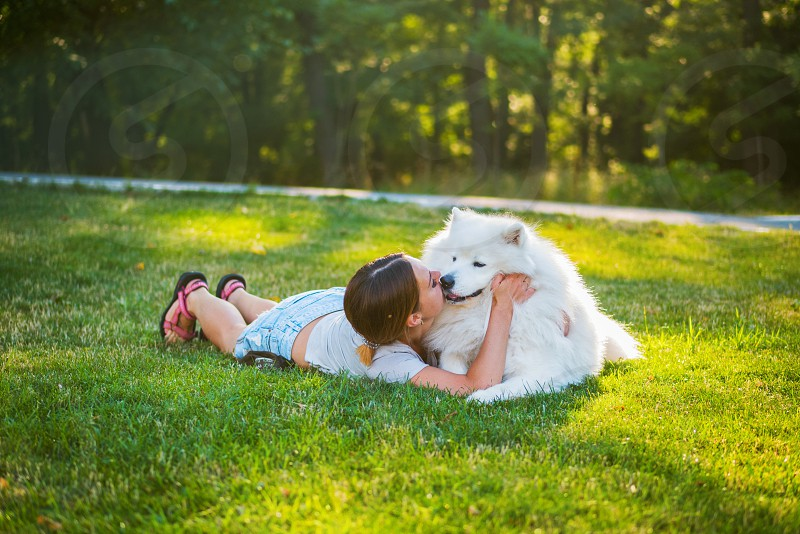 Young woman playing with her big fluffy dog Samoyed in park photo