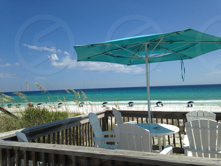 white armchairs and umbrella on wooden dock near beach photo