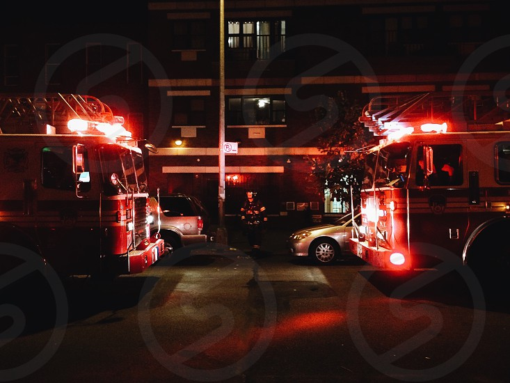 2 fire trucks with lights on parked in street during night time photo