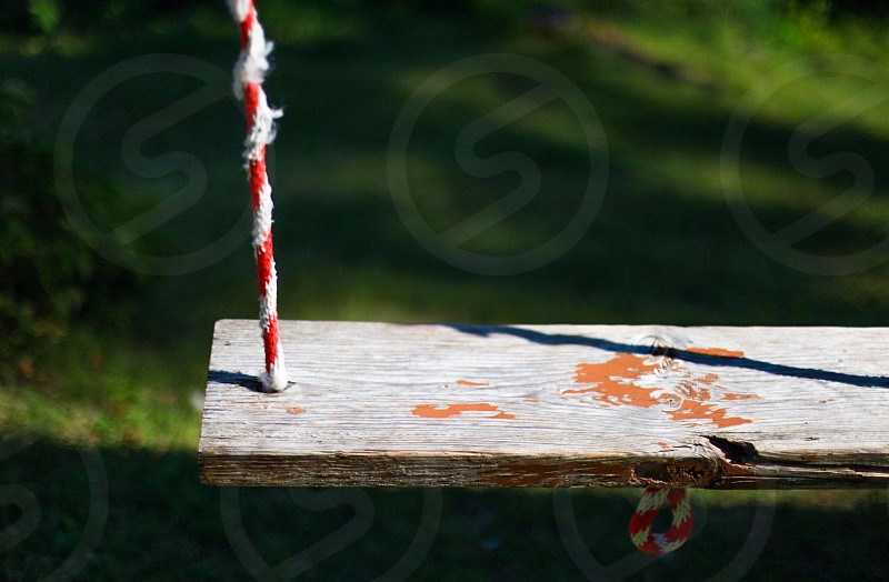 wooden swing with red and white string photo
