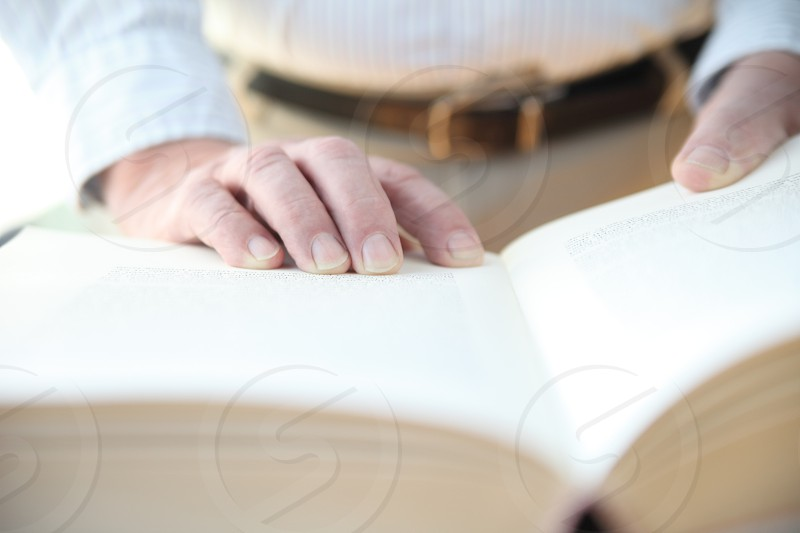 Man with his hands on a large book photo