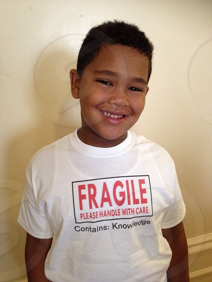 boy smiling in white t shirt with fragile handle with care design photo