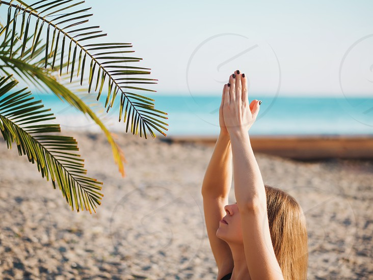 Beautiful young woman practicing morning yoga in lotus pose on tropical sea beach with tree palms. photo