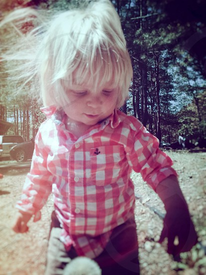toddler in red white checked dress shirt standing while looking down photo