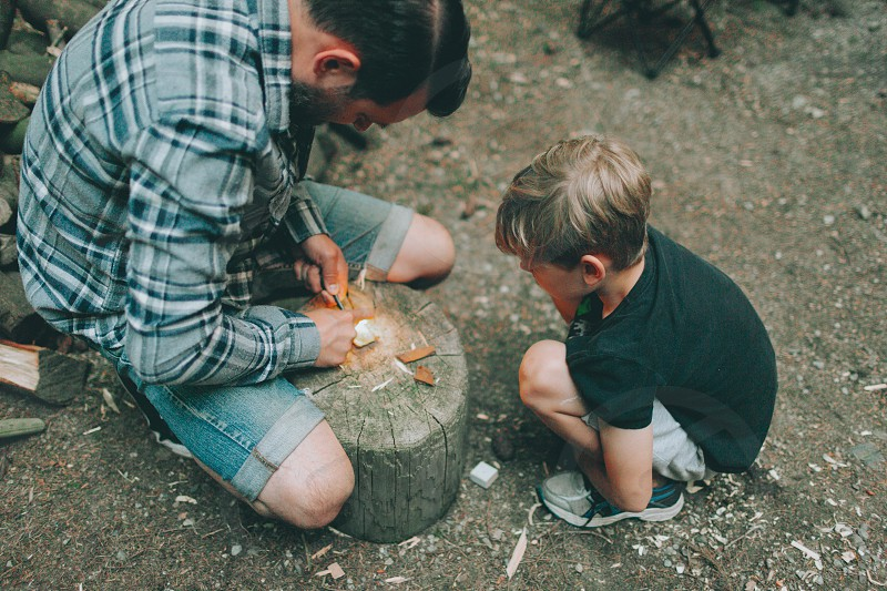 A father teaching his son how to start a fire.  photo