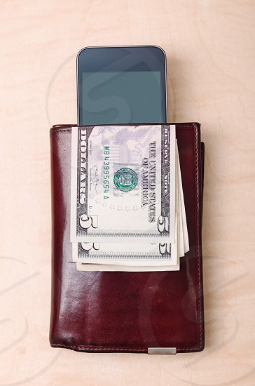 Wallet smartphone with blank screen and dollar banknotes on wooden table. View from above. Portrait orientation photo