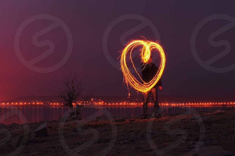 man in black jacket holding a sparkler forming it a heart shape photo