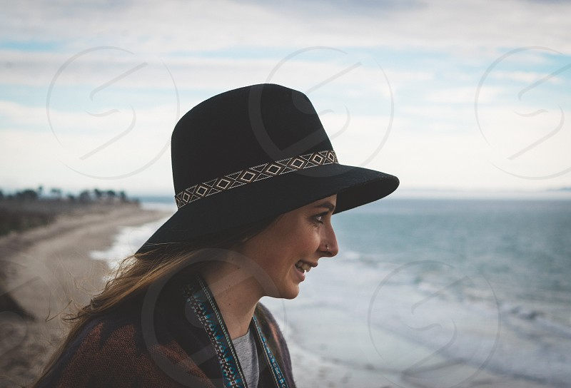 woman in brown coat wearing black hat staring at the blue and white sea during day time photo