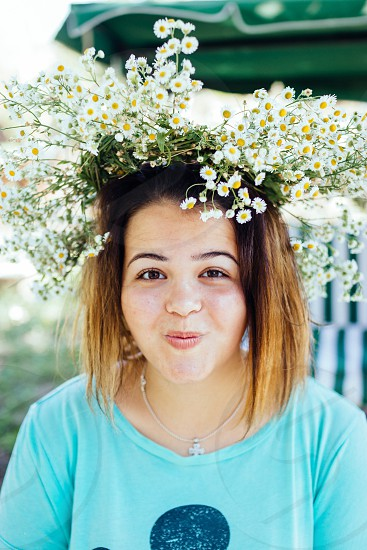Redhead woman with wreath on her head makes silly face looking into camera photo
