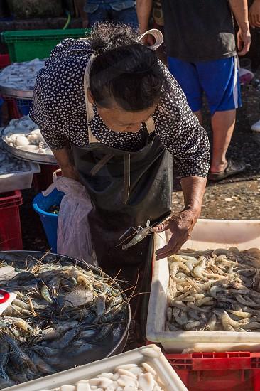 Seafood market - woman selling fresh seafood in Bangkok Thailand photo