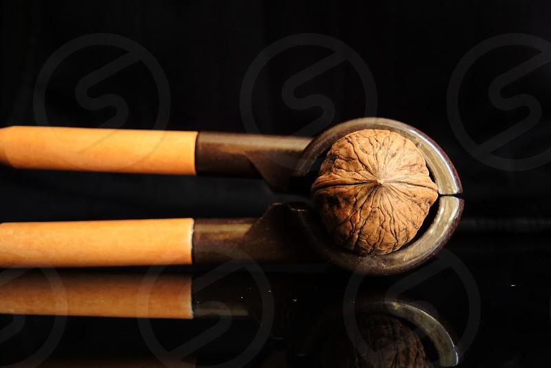 brown nutcracker with walnut in dark background photo