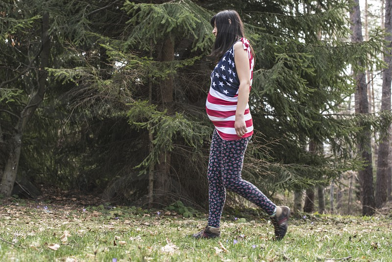 Pregnant woman in the forest. American national flag shirt photo