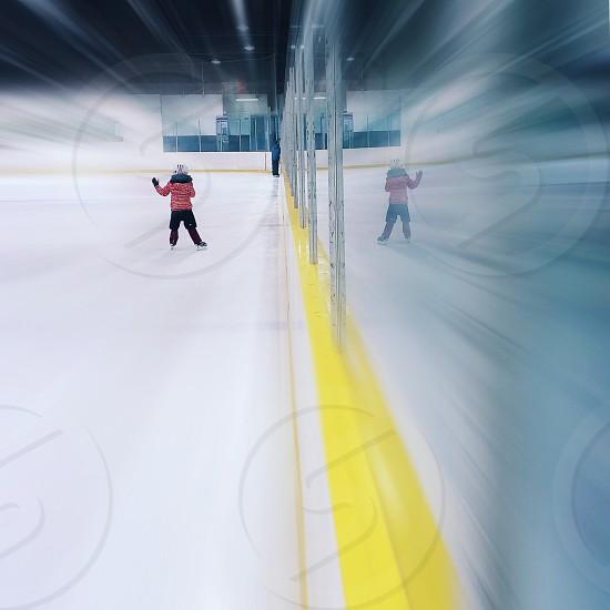 person wearing red striped sweater and black shorts in ice rink photo
