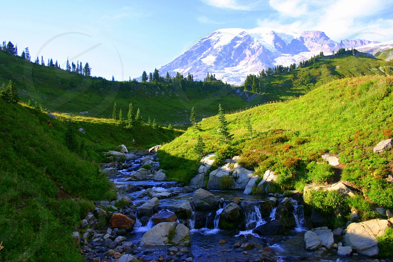 snow capped mountain and green valley with stream photo