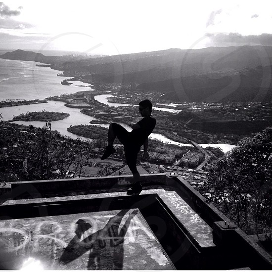 grayscale photo of person balancing on top of metal bars above city photo