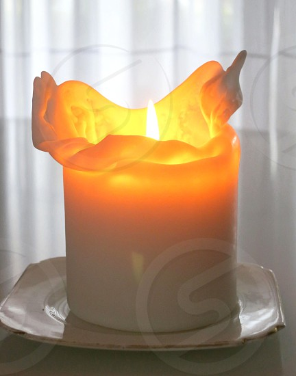 White candle golden flame white background photo